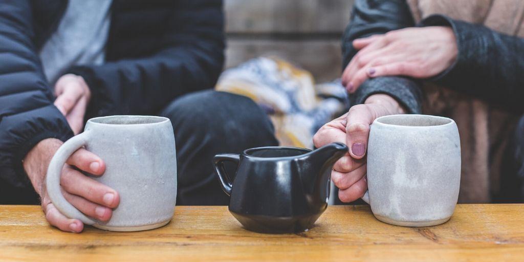 warme thee gezellig twee koppen zwarte theekan handen